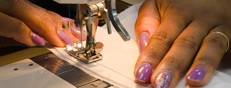 Hands working fabric under sewing machine
